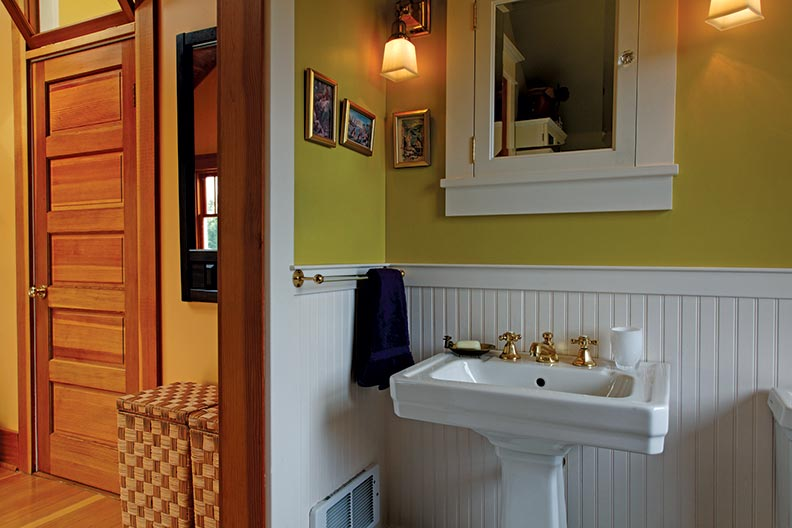 The master bathroom was carved out of a former closet, and combines vintage features like an inset medicine cabinet and pedestal sink with state-of-the-art conveniences like tile floors warmed by radiant heat.