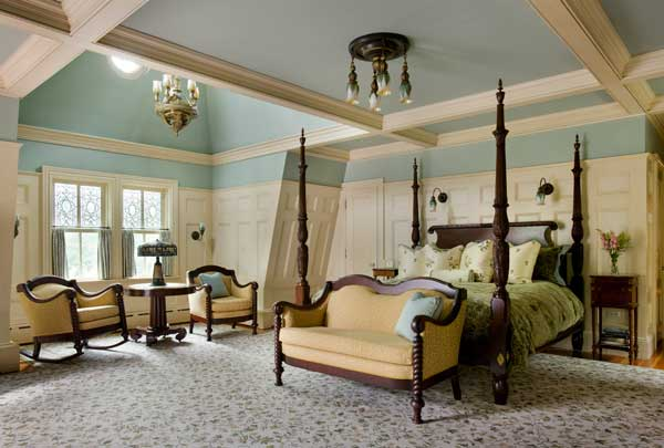 The master bedroom soars into the added rear tower. Vintage lighting, and an urn-top four-poster bed from Leonard's New England lend antiquity.