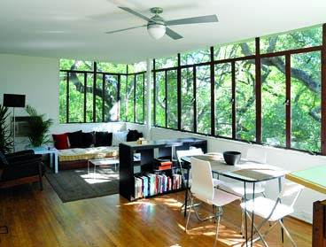 The mid-century dream of seamlessly merging indoors and out comes to life in a sitting room surrounded by live oaks.