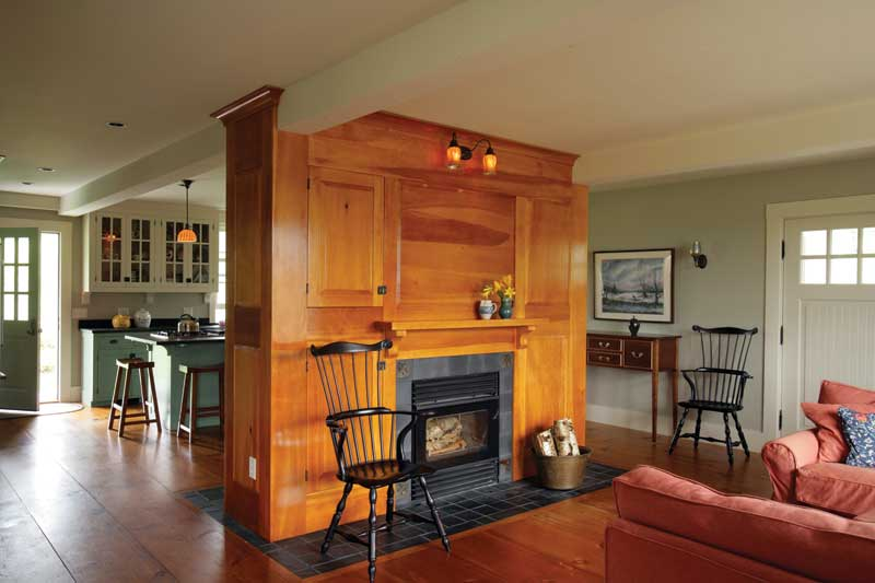 The new family room and kitchen are divided with a freestanding fireplace and mantel.