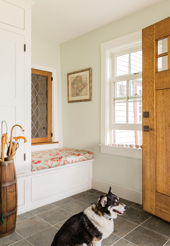 The new mud room has tile flooring, a built-in bench, and a diamond-paned window that brings light into the new half bath.