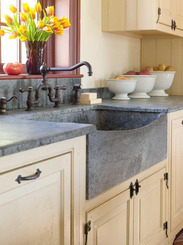 The new space has such traditional features as a scoop-front soapstone sink and storage hidden in furniture-quality cabinets.