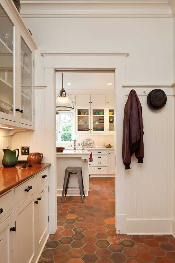 The old butler's pantry became a mudroom with pantry counter and a powder room; the view is into the kitchen.