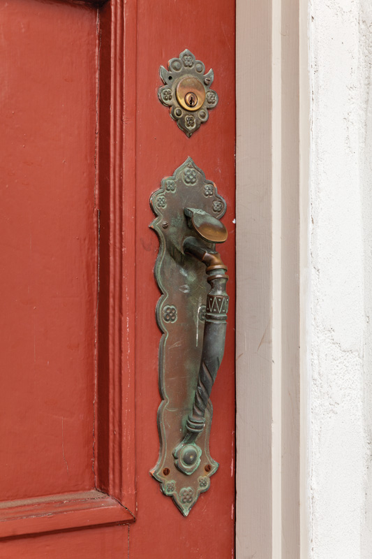 The original bronze entry hardware is ornate.