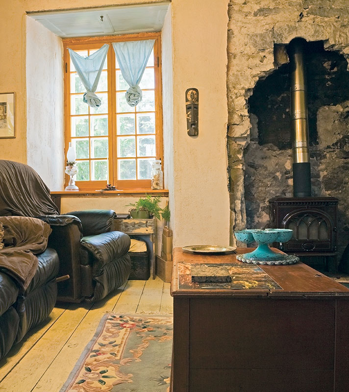 The other side of the living room is a nook with cozy sofas and a wood stove.