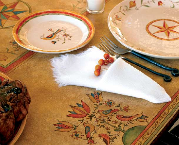 "The owners made the painted table cover in a design called ""Meadow""; the dish pattern is ""Star Fraktur."""