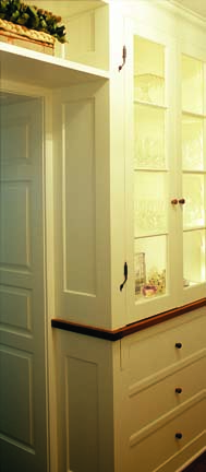 The pantry is fashioned after traditional Philadelphia pantries: white glass-front cabinetry with small rat-tail hinges and wooden knobs.