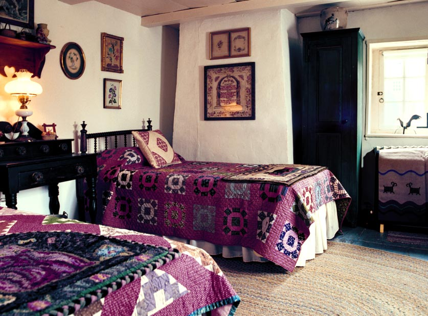 The quilts and rugs in a bedroom are from the town of Hurley.