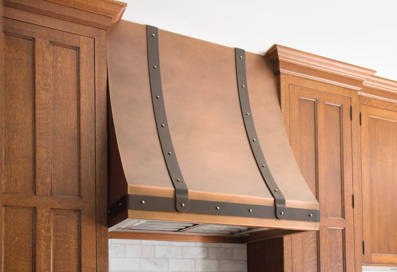 The range hood is hand-hammered copper with brass straps.