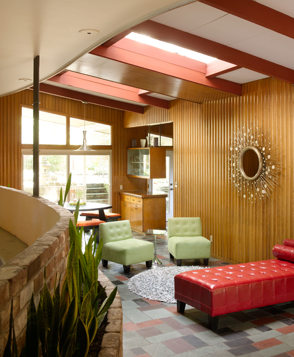 The red daybed and green slipper chairs create a conversation area in the middle of the open living space. The starburst mirror is vintage, ca. 1960. Floating shelves separate the dining area from the kitchen.
