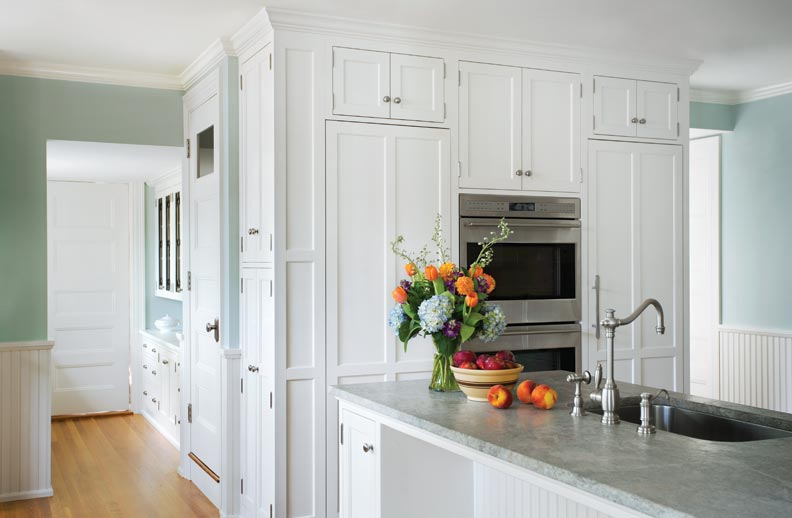 The refrigerator and freezer are hidden behind panels that match the cabinetry.