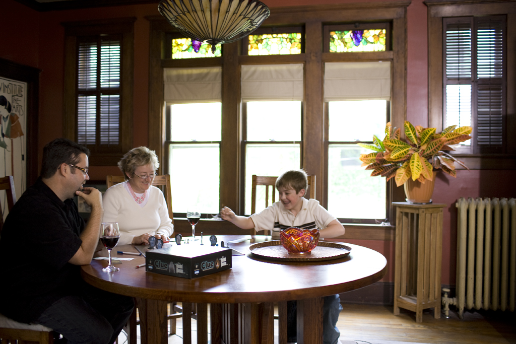 The refurbished dining room, a hub for family fun, features grape-motif stained-glass transoms, among the many original art glass windows in the home.