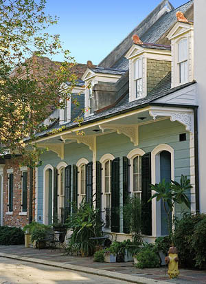 This six-bay Creole cottage designed by Mike Waller is, in fact, a pair of townhouses. The large four-over-four front windows with segmental arches were salvaged from the St. Joseph Church rectory in New Orleans. The Victorian ornamental brackets adorning the roof overhang were purchased from a New Orleans salvage yard.