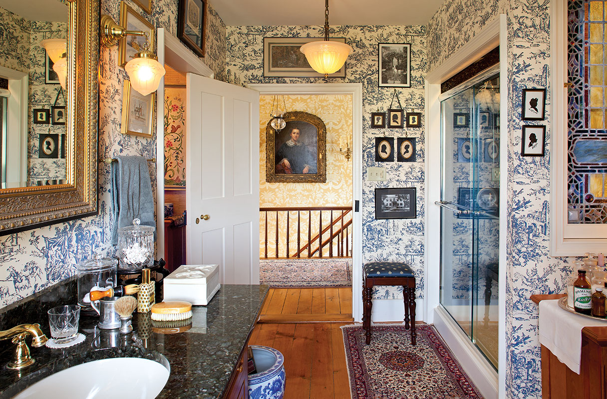 "The smallest of four second-floor bedrooms became a ""furnished"" bath papered in blue-and-white toile. Pictures of favorite historic houses hang alongside collected silhouettes."