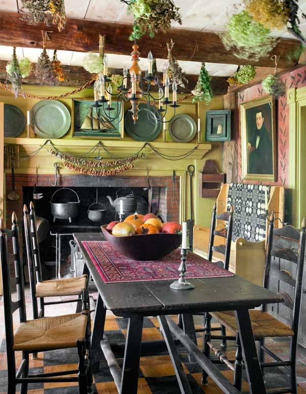 The tavern room, which serves as the main entrance, is also the breakfast room. Clusters of drying herbs hang over antique furnishings.