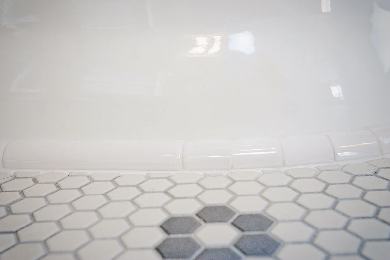 The tub's finish edge of quarter-round tile hides a visible difference in its support, owing to the floor's extreme pitch.