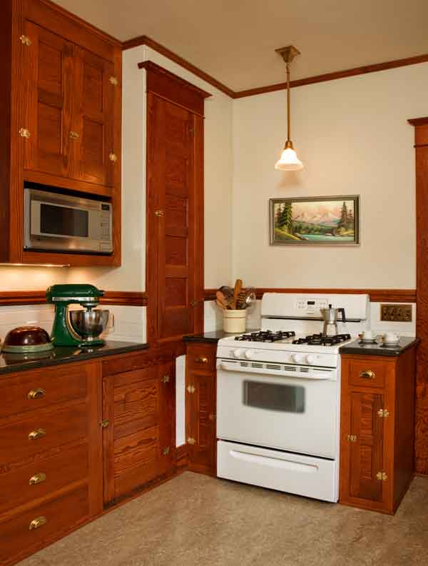 The unused wood lift was refitted with pantry shelves. This view shows old and new cabinets, well matched. (A four-year-old stove remains.)