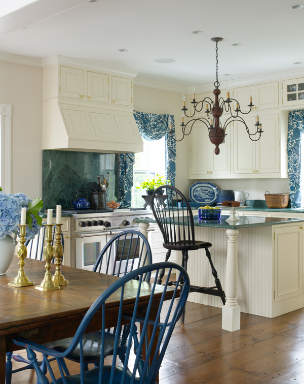 The warmth of the old floor anchors the crisp blue-and-white kitchen. The owner painted her antique English Windsor chairs blue.