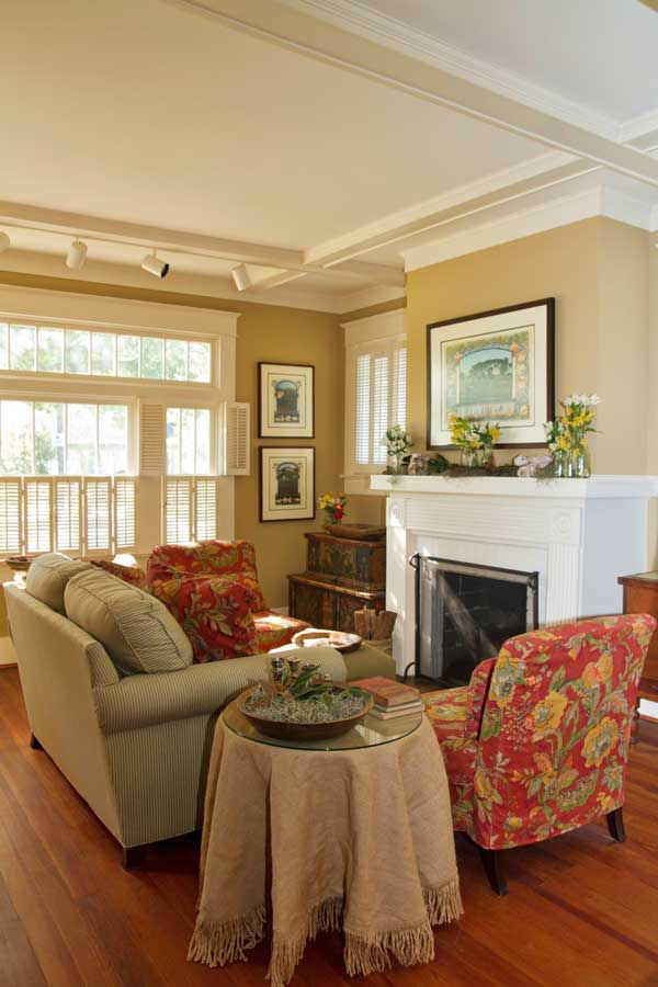 The wide living room features a long bank of windows with interior shutters; pretty antique samplers add history.