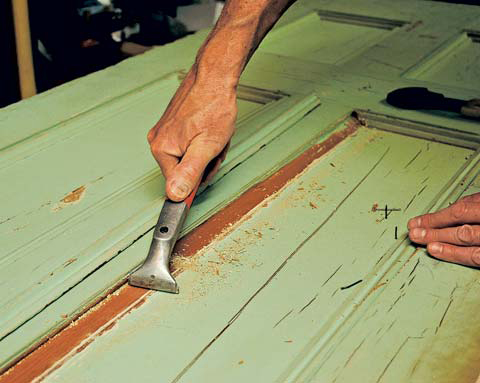 Carbide scraper stripping paint off an old door