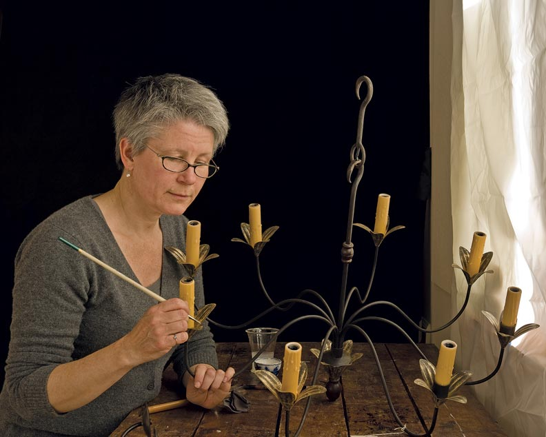 The company has skilled craftspeople such as Roz Cristinson, shown here gilding a fixture by hand, to create one-of-a-kind pieces.