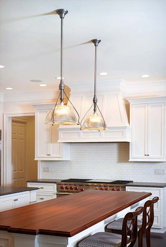 Industrial-style pendants feature Holophane shades.