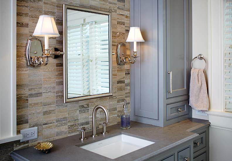 Traditional sconces flank a bathroom mirror.