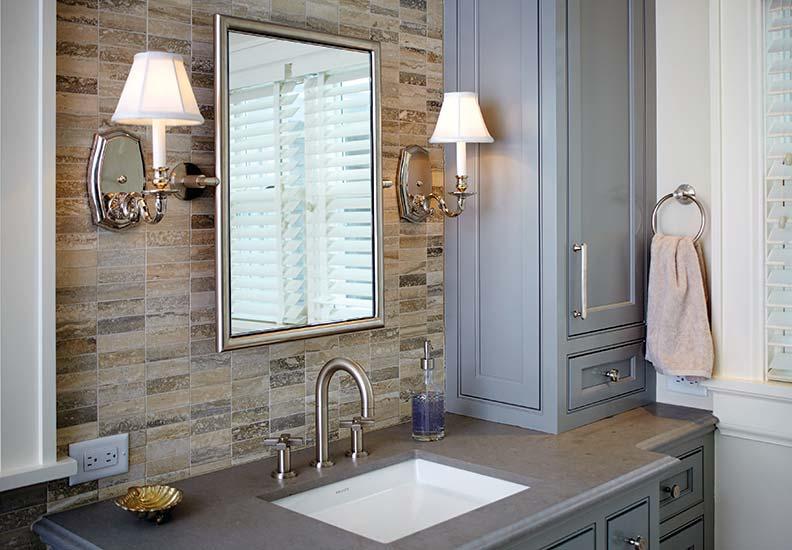 Traditional sconces flank a bathroom mirror.