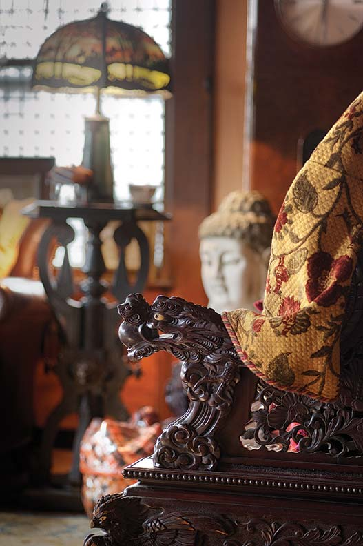 Treasures from Africa and the Far East fill the living room; the Chinese carved mahogany bench is ca. 1900.