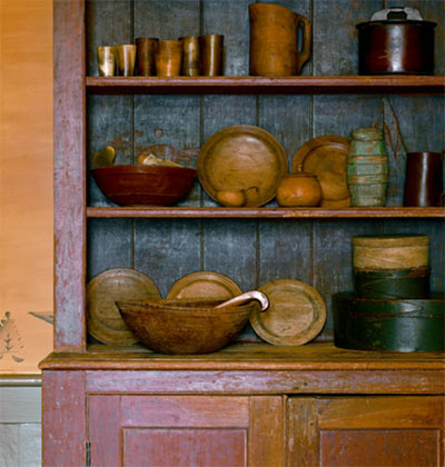 Treenware plates, bowls, and a pitcher or two coordinate peacefully with other wood items on a cupboard with aged milk paint.