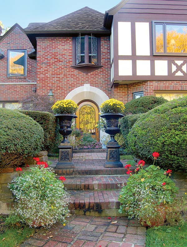 Before the Ryans added flowers, the yard was manicured but monochrome. Now plantings define space; antique iron urns add stately aplomb and seasonal color.
