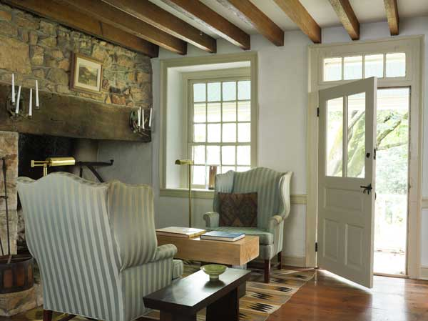 Upholstered wing chairs sit by the original hearth in what would have been the keeping room or kitchen in the old house.