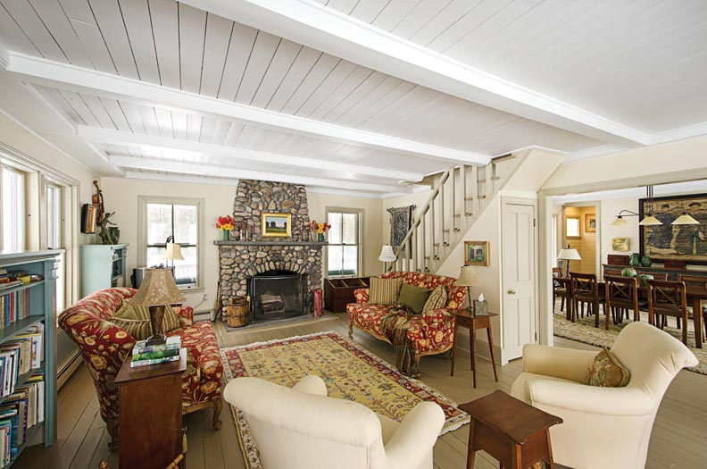 A fieldstone fireplace anchors the living room, which is separated from the dining room by a staircase.