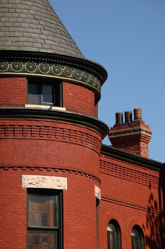 Victorian gaslights are still gas-lit in the 1891 Queen Anne tower house that occupies a corner lot.