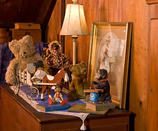 Vintage toys highlighted by a Steiff bear are shown against a ca. 1913 portrait of a child holding the same bear, in a tableau that tells a story. (Photo: Edward Addeo)