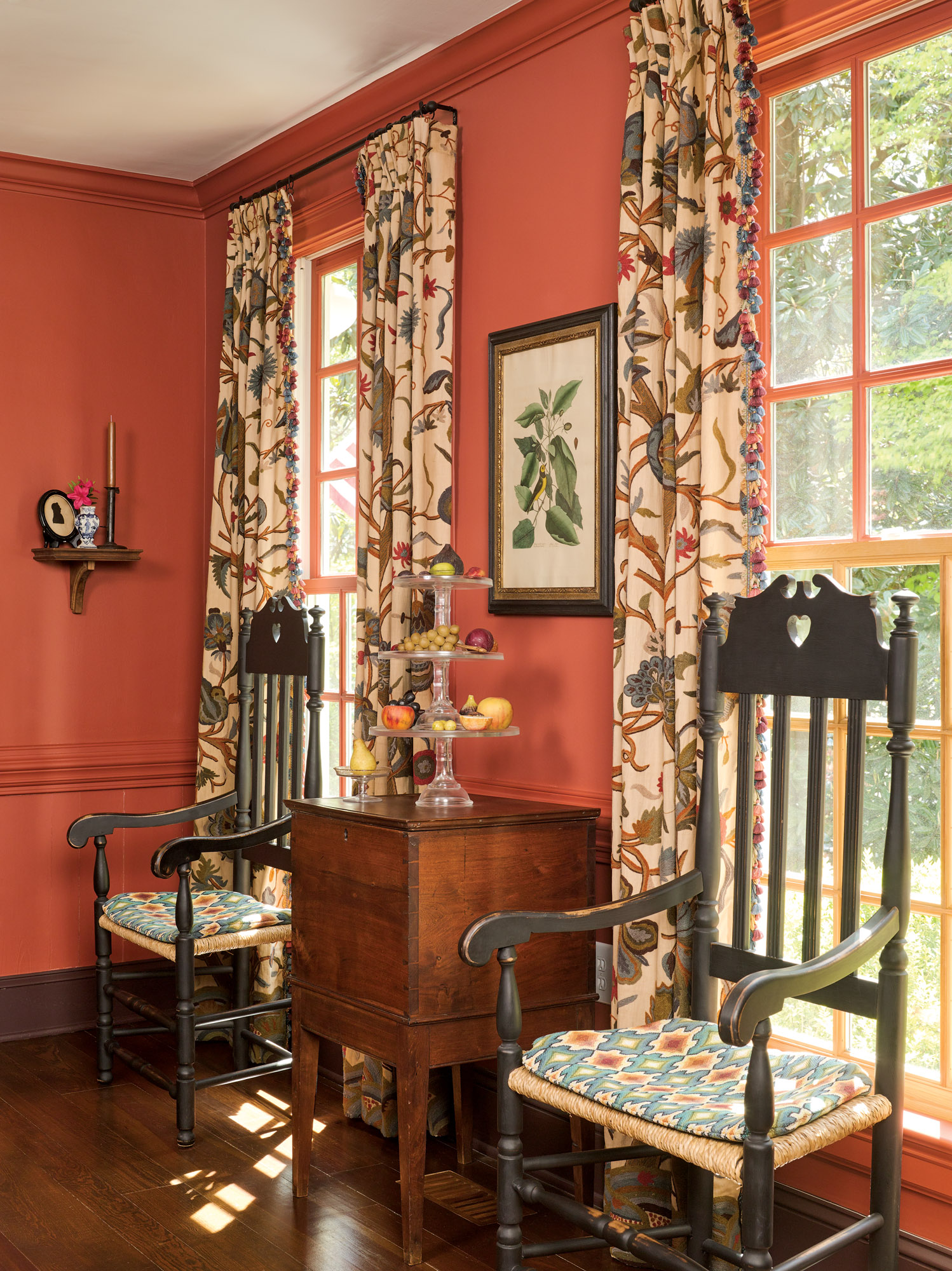 The salmon-red dining room has antique crewel fabric at the windows. Antique stone fruit on a glass étagère is displayed on the antique cellarette (bottle case) between reproduction banister-back chairs.