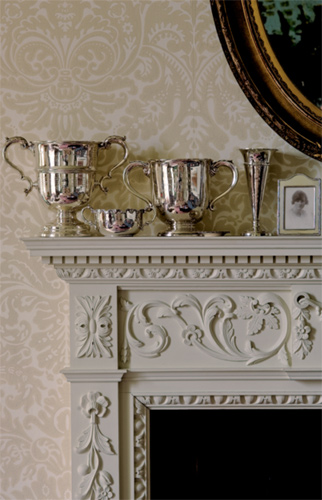 The 'Silvergate' damask paper from Farrow & Ball repeats swirls of classical decoration in the mantel; the look is serene rather than busy because of the neutral colors and similar tones.