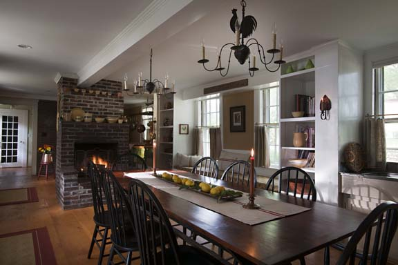 The south end of the kitchen is centered on a sawbuck dining table milled from lumber salvaged from an old shed on the property. Built-in bookcases, a 10'-long window seat, and the centered hearth make the long room cozy and comfortable.