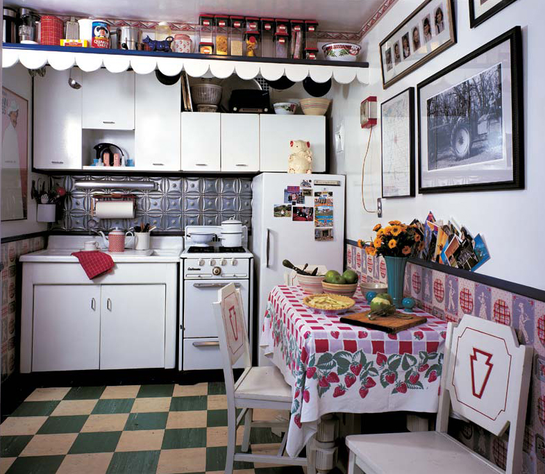 The ca. 1940 kitchen was designed around vintage wallpaper of that period, purchased as old stock by the owner. Remnant floor tiles, tin backsplash, and modern cabinets and pulls all evoke the period. Red and white chairs are perfect for the room, as are such collectibles as the elephant cookie jar by McCoy.