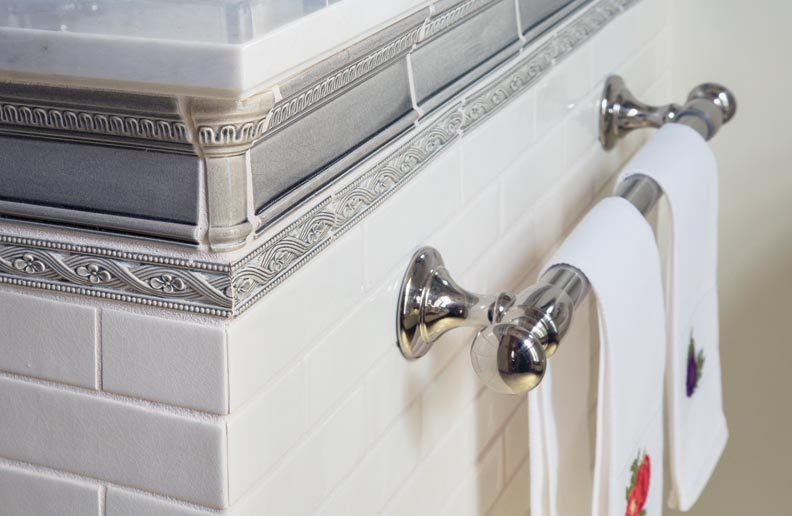 White subway tile is bordered with a decorative gray tile.