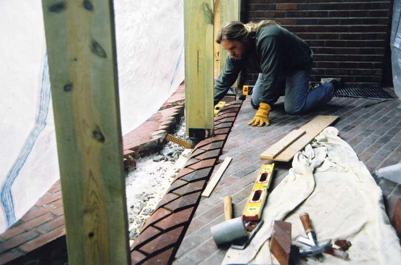 """Stafford Norris works to install the new threshold, which protrudes 7/8"""" above the old floor to help keep water out."""