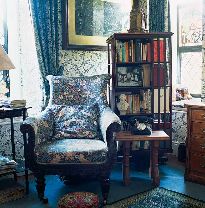 William Morris fabric was used to upholster the high-back chair; original Morris curtains were found for the study's windows.