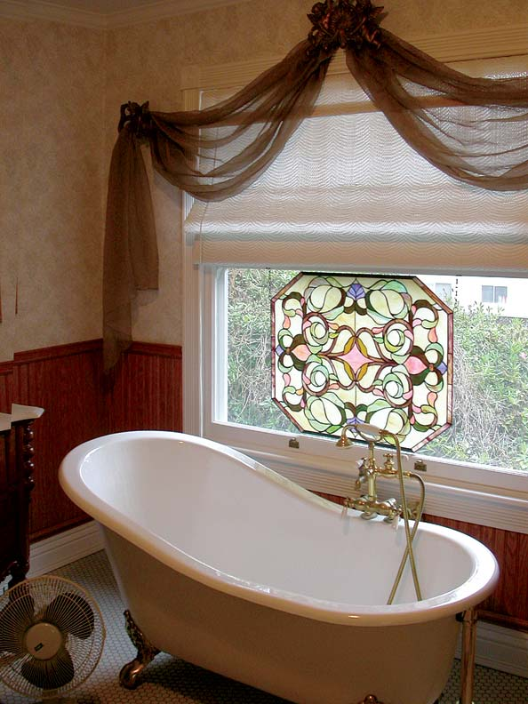 While a stained-glass panel offers a jolt of bright color, a roller shade from Alameda Shade Shop ensures complete privacy.