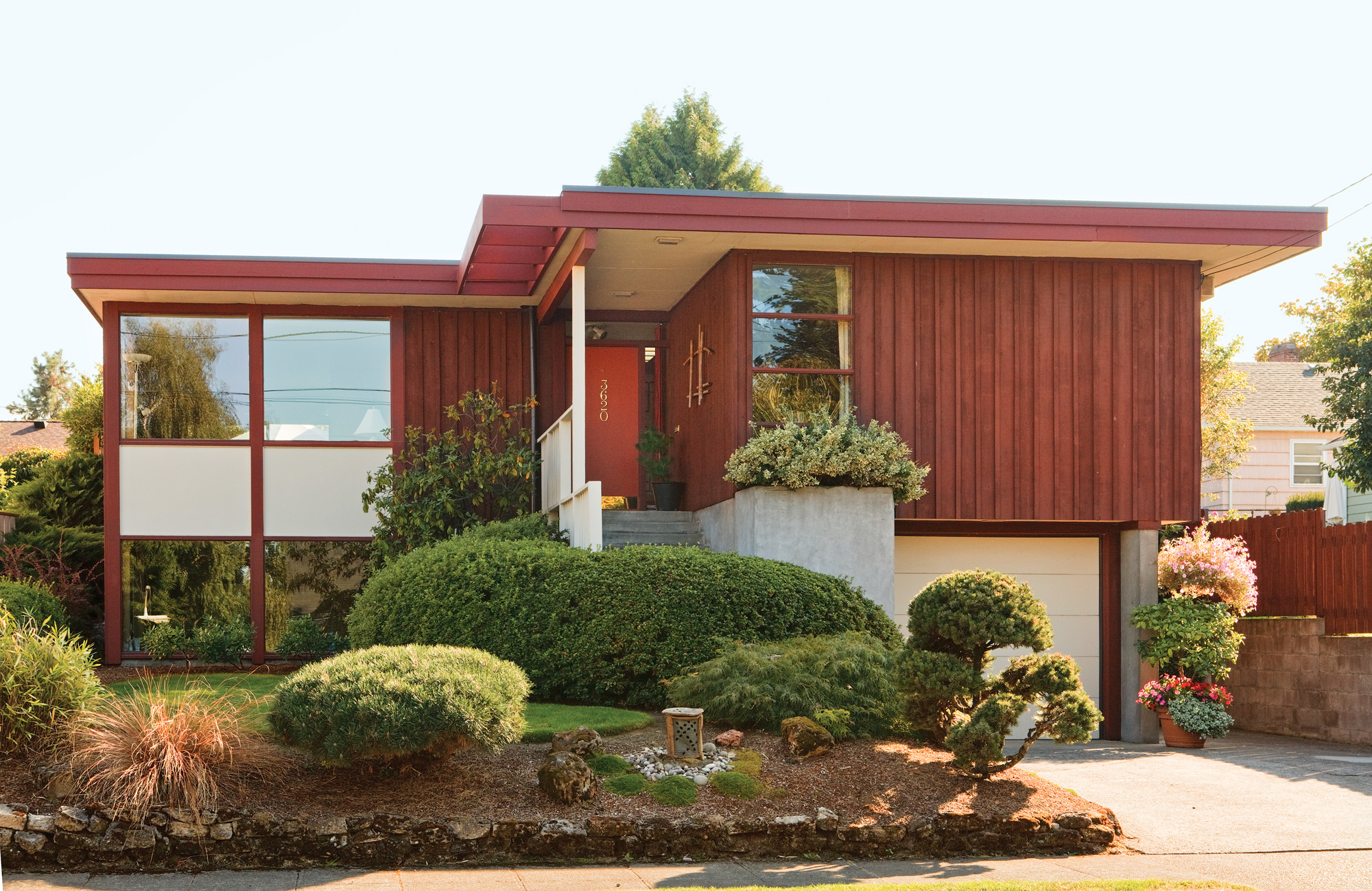 A 1955 Usonian-influenced house with cedar board-and-batten siding and  a nearly flat roof exhibits some  of the attractions of mid- century architecture, from  horizontal emphasis to  oversized windows.