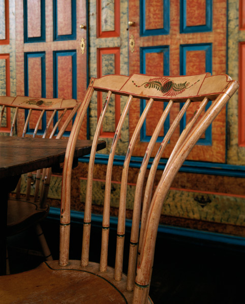 The salmon-painted, step down Windsor side chairs date from the early 19th century.