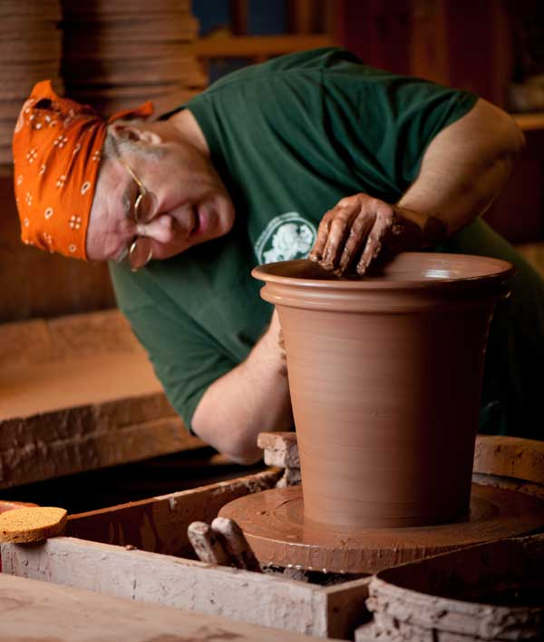 With ten pounds of clay on the wheel, Guy Wolff deftly shapes the Georgian rim of a pot inspired by terra cotta he found in several 18th-century collections.