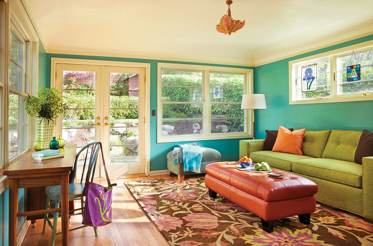 The color-drenched family room in the new wing sparkles with light coming in from three directions. The coved ceiling mimics originals in the house. A vintage 50s floor lamp and desk add to the period feel. The rug (nwrugs.com) pulls together the kaleidoscopic colors.