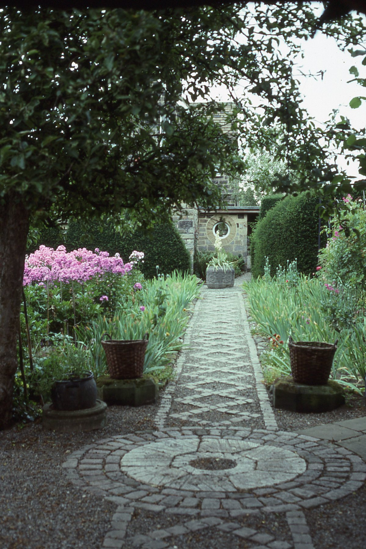 A diamond-patterned stone path leading from the home is the focal point of a Yorkshire garden.